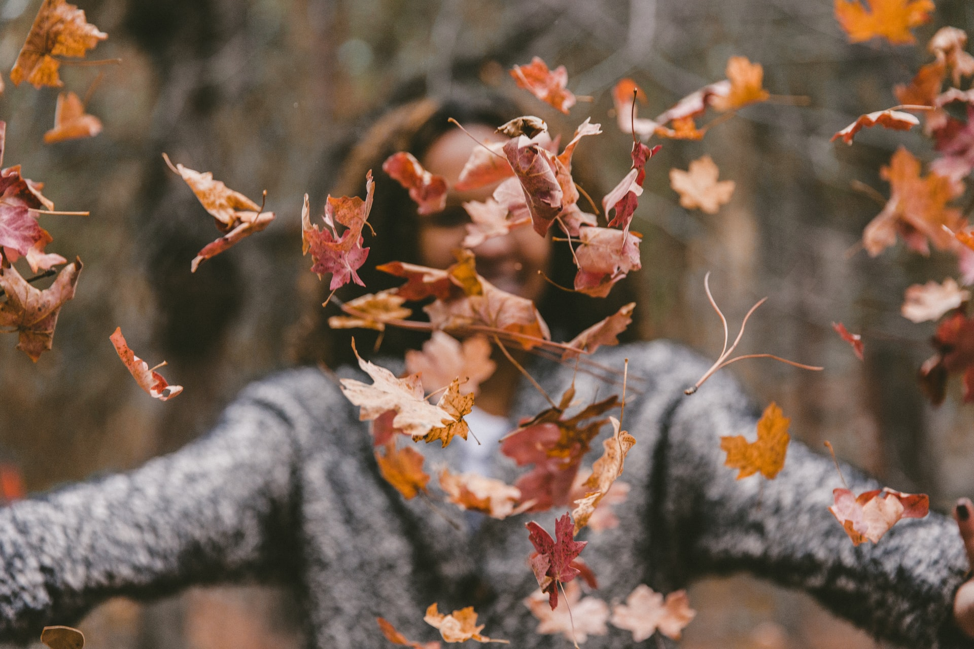 woman throwing autumn leaves